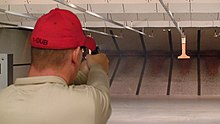 Indoor firing range showing walls, ceiling baffles, and bullet trap